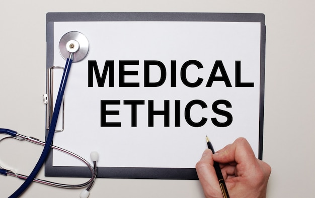 On a light surface, a stethoscope and a sheet of paper, on which a man writes medical ethics