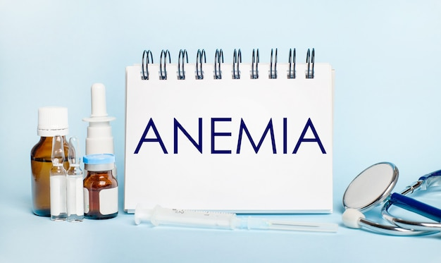 On a light surface, a syringe, a stethoscope, vials of medicine, an ampoule and a white notepad with the text anemia. medical concept