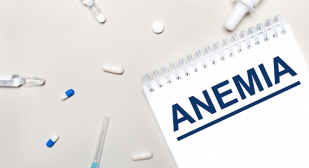 On a light surface, a syringe, a stethoscope, vials of medicine, an ampoule and a white notepad with the text anemia