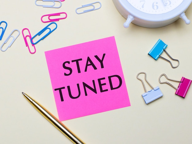 On a light surface, a white alarm clock, pink, blue and white paper clips, a golden pen and a pink sticker with the text stay tuned
