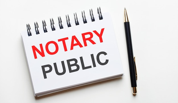 On a light surface, a white notebook with are words notary public and a pen