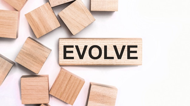 On a light surface, wooden cubes and a wooden block with the text evolve. view from above