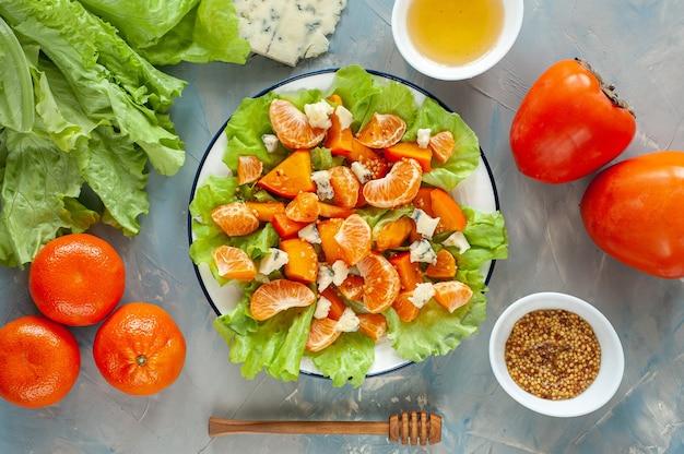 Легкий кисло-сладкий салат с хурмой, мандаринами и голубым сыром. зимний витаминный салат и ингредиенты на синем столе. диетическое питание. вид сверху.