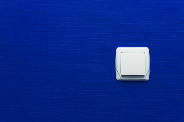 Выключатель на синем фоне стены. дизайн интерьера. минимальный стиль.