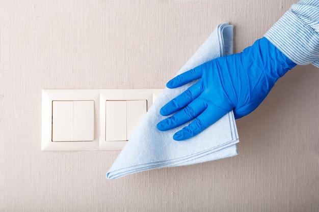 ライトスイッチの表面消毒。濡れた雑巾で壁に布を付けた、ゴム製の青い手袋のきれいな光スイッチの女性新しい通常のcovid 19コロナウイルスの消毒、家の掃除。家事掃除サービス。