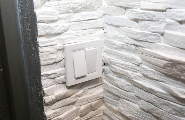 電気のスイッチ。装飾的なレンガとコンクリートの背景を持つ壁。メンテナンス修理作業。フラットでの改修。屋内での修復。