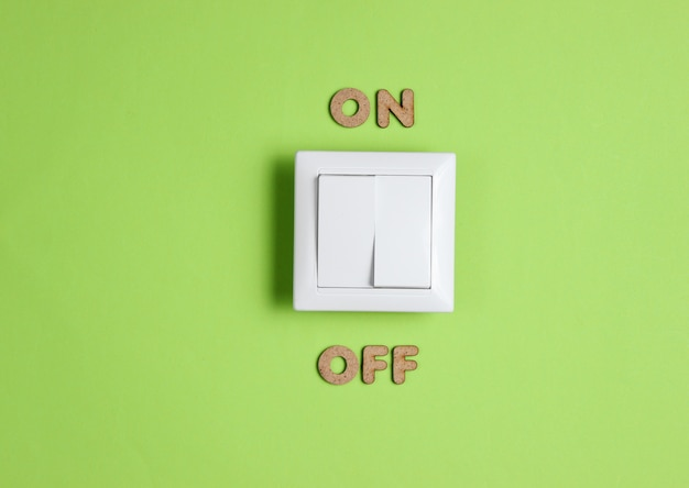 Light switch with on off word on green surface