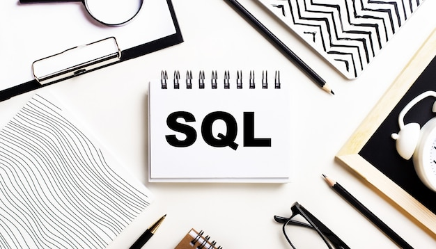 On a light table are notebooks, a magnifying glass, an alarm clock, glasses, and a pen. and in the center is a notebook with the text sql