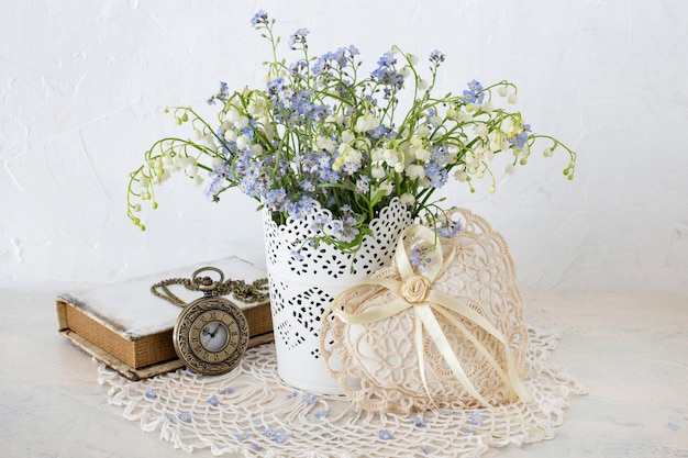 On a light table, forget me nots and lilies of the valley are placed in a vase, a book, a heart