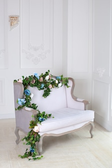 Light textile classic sofa in a vintage room. a light classic royal interior with a soft sofa with a fabric upholstery. elegant royal luxury interior with white walls and gray sofa. relaxation