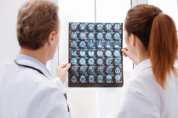 助けるために光。彼の診断と治療について話し合いながら患者の脳スキャンを検査する2人の有能な決定された脳神経外科医