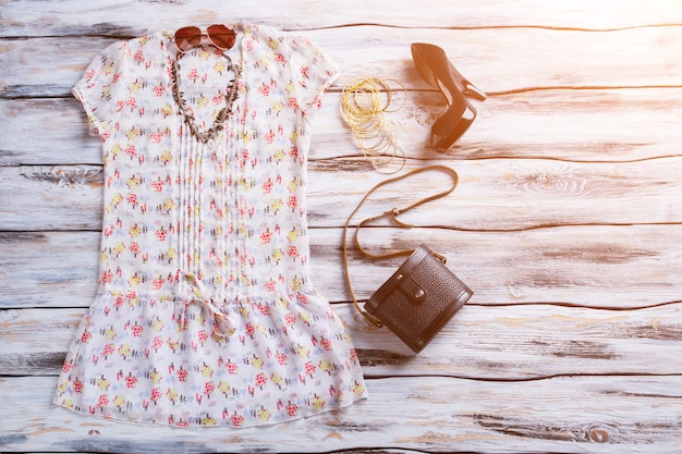 明るいトップと暗いヒール。黒のヒールの靴と財布。女性の魅力的な夏の装い。日光の下でスタイリッシュな服。