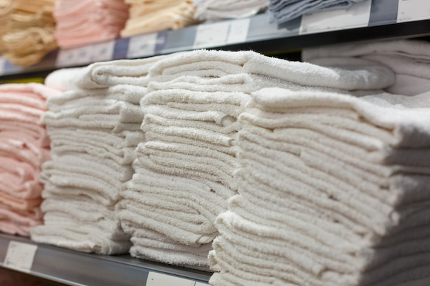 Light towels in stacks on the shelf in the store, textile section in the store