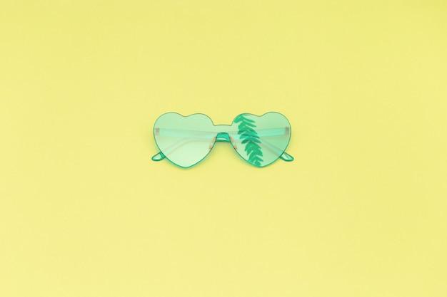 야자수 잎의 그림자와 함께 밝은 청록색 현대 선글라스. 프리미엄 사진