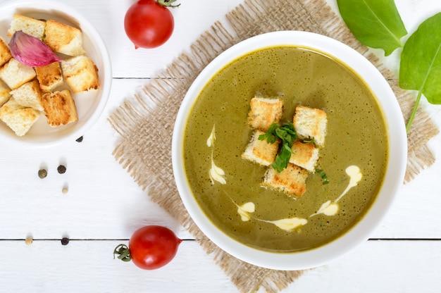Легкий веганский крем-суп из шпината с хрустящими гренками в миске на белом