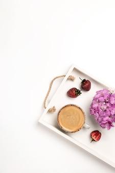 コーヒーイチゴのカップと白いテーブルで製品のプレゼンテーションのための軽い垂直モックアップ...