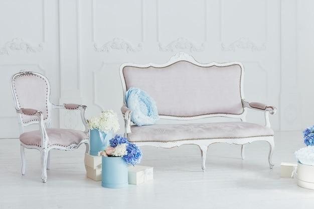 Легкий диван и кресло в винтажном стиле и ящики с цветами