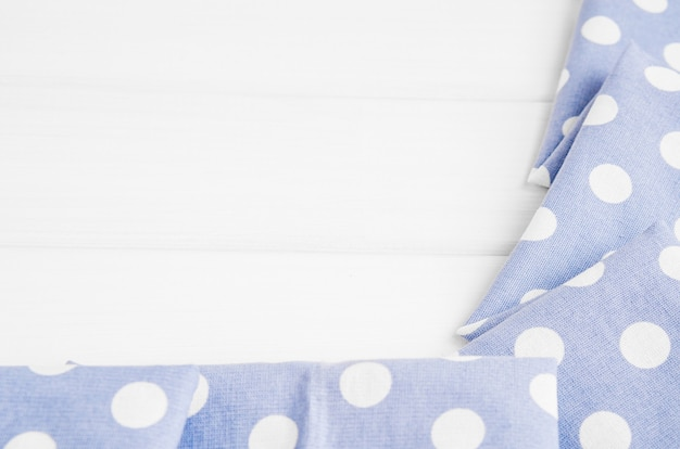 Light violet blue polka dots folded tablecloth over bleached wooden table. top view image. copyspace