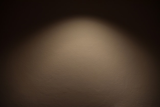 Light on wall - the lamp shines with warm light on brown wall / light effect