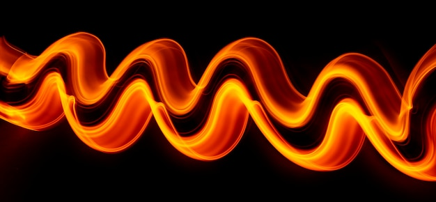 Light wave trail path, vibrant neon gold color in abstract swirls on a black background. light painting