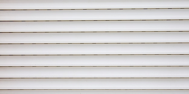 Light white curtain backdrop close-up modern plastic shutter blinds in office room home plastic panels texture background