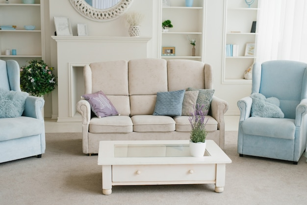 Light with blue living room: sofa, armchairs, fireplace and shelves with decor, part of the mirror