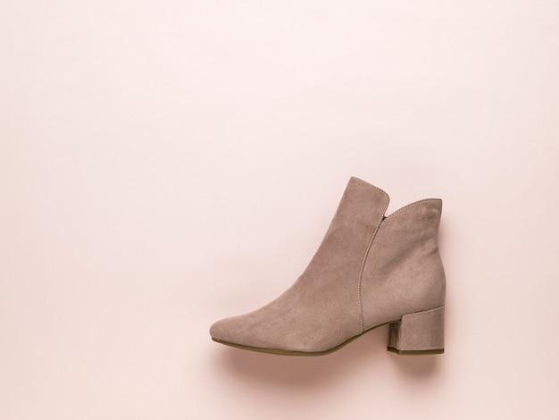 Light women's beige suede boot on a light beige . stylish demi-season women's shoes. flat lay.