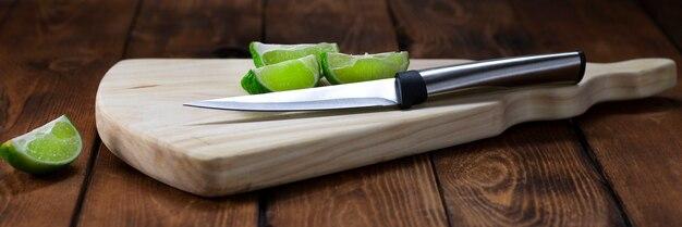 Разделочная доска из светлого дерева с ножом и кусочками лайма на деревянном столе