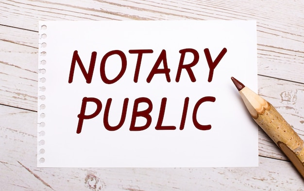 On a light wooden background, a colored pencil and a white sheet of paper with the text notary public