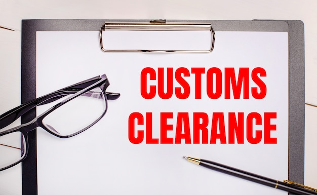 On a light wooden background glasses, a pen and a sheet of paper with the text customs clearance. business concept