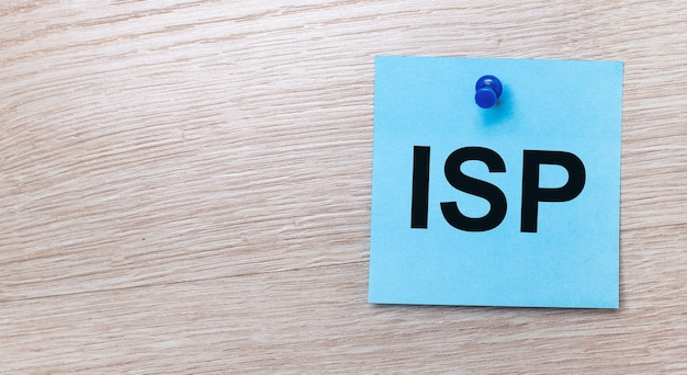 On a light wooden background - a light blue square sticker with the text isp internet service provider