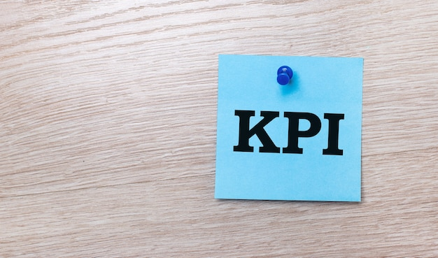 On a light wooden background  a light blue square sticker with the text kpi.