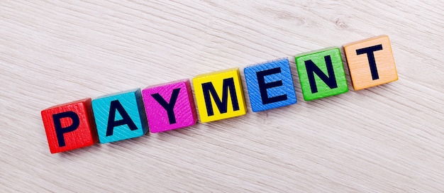 On a light wooden background on multi-colored bright wooden cubes the word payment