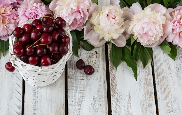 On a light wooden background pink peonies and cherries in a white wicker basket