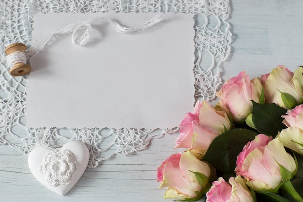 On a light wooden background a sheet of paper, pink roses, a heart, rose petals
