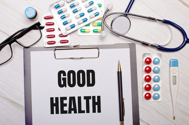 On a light wooden background there is paper with the inscription good health, a stethoscope, colorful pills, glasses and a pen