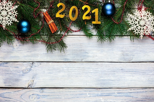 Light wooden christmas background with  lettering blue christmas balls fir branches white snowflakes...