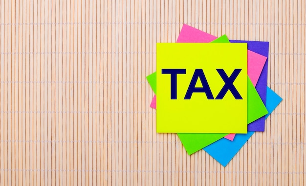 On a light wooden surface, bright multicolored stickers with the text tax