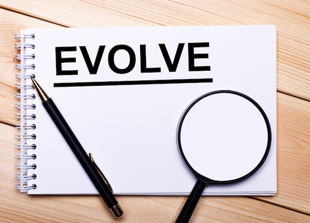 On a light wooden surface lie a pen, a magnifying glass and a notebook with the text evolve