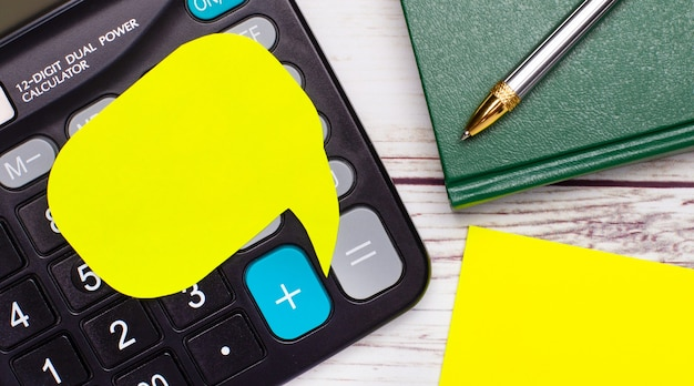 The light wooden table has a calculator, a green notebook, a pen, yellow paper, and a yellow card with space to insert text. business concept.