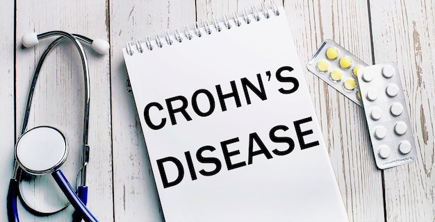 On a light wooden table lie a stethoscope, pills and a notebook with the inscription crohn s disease
