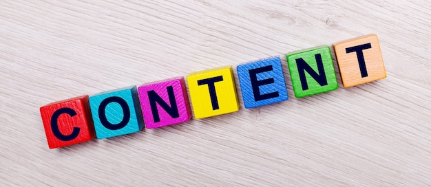 On a light wooden table on multi-colored bright wooden cubes the word content