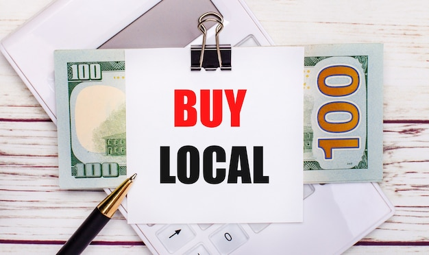 On a light wooden table, there is a white calculator, a pen, bills, and a sheet of paper under a black paper clip with the text buy local. business concept
