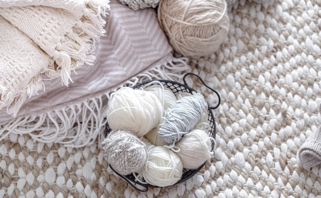 Light yarn for knitting in a basket with knitted elements.