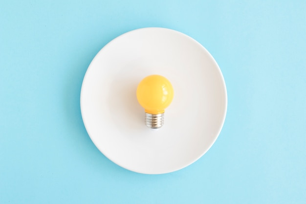 Light yellow bulb on white dish over the blue backdrop