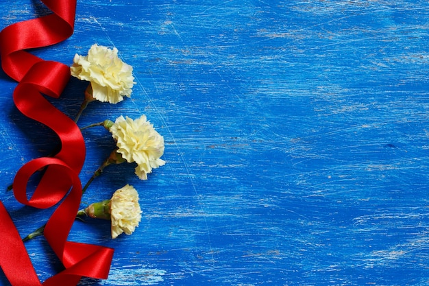 Light yellow carnations with red silk ribbon on blue surface