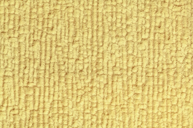 Light yellow fluffy background of soft, fleecy cloth. texture of textile closeup.