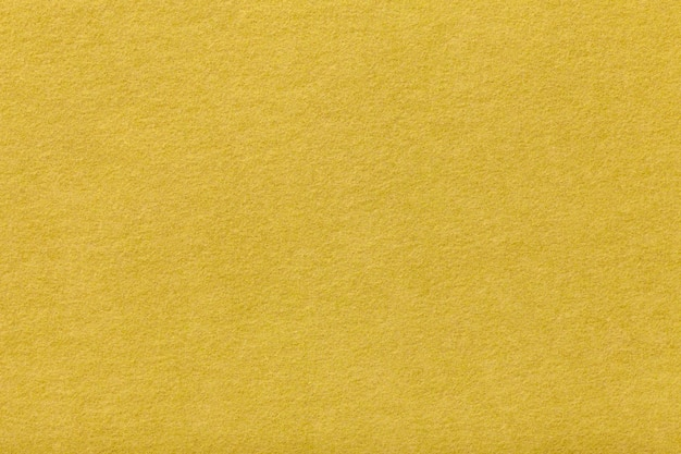 Light yellow matt suede fabric. velvet texture of felt background
