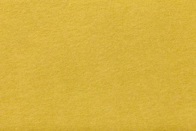 薄黄色のマットスエード生地。フェルトの背景のビロードのテクスチャ