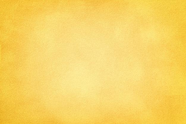 Light yellow matte background of suede fabric with dark vignette. velvet texture of golden felt textile with gradient, macro.